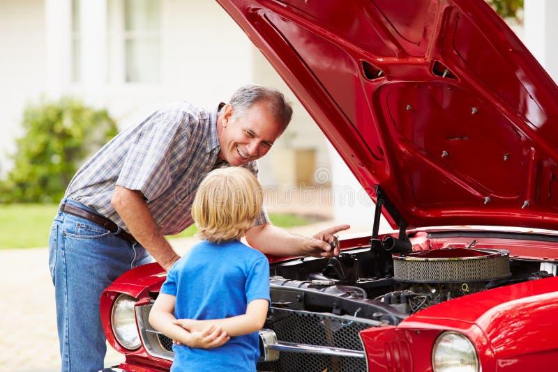 Farfar och sonson som arbetar på den återställda klassiska bilen royaltyfri fotografi