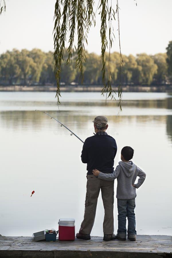 Farfar och sonson som fiskar av av skeppsdocka på sjön royaltyfri foto