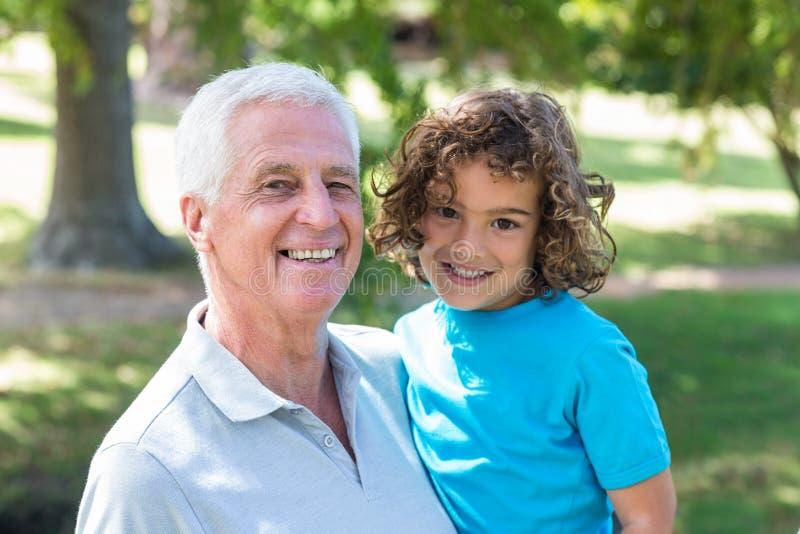 farfar och sonson som har gyckel i en parkera royaltyfria bilder