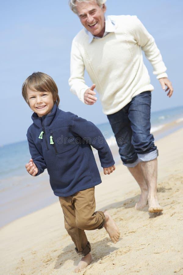Farfar och sonson som kör längs strand royaltyfri bild