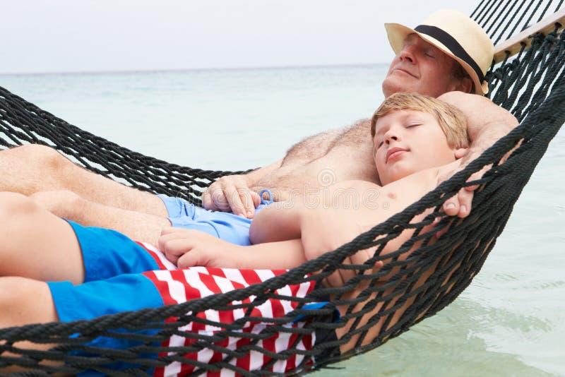 Farfar och sonson som kopplar av i strandhängmatta arkivfoton