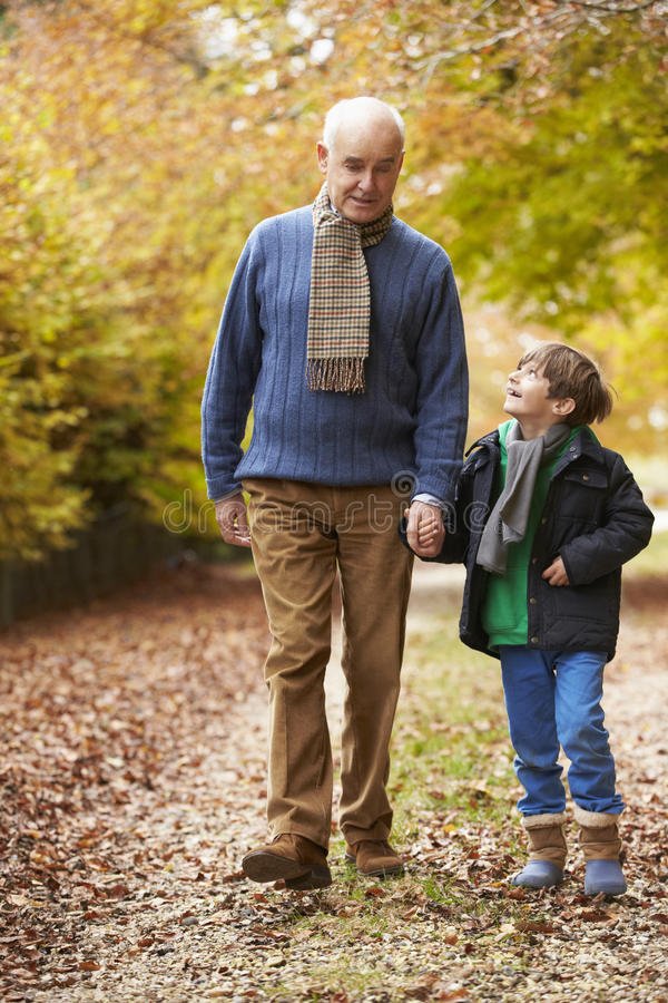 Farfar och sonson som promenerar Autumn Path royaltyfria bilder