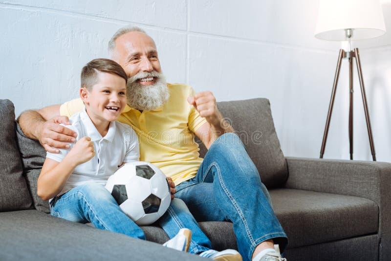 Farfar och sonson som rotar för deras favorit- fotbollslag royaltyfri bild