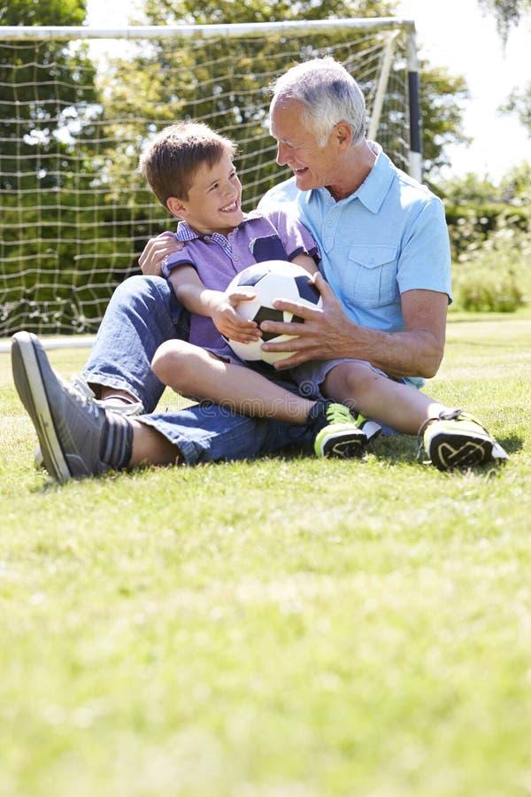 Farfar och sonson som spelar fotboll i trädgård royaltyfria bilder