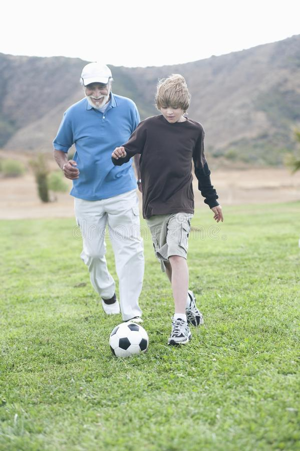 Farfar och sonson som spelar fotboll på fält royaltyfri fotografi