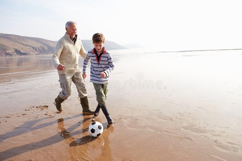 Farfar och sonson som spelar fotboll på vinterstranden arkivbilder