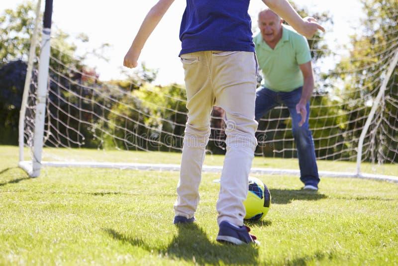 Farfar och sonson som spelar fotboll tillsammans royaltyfri foto