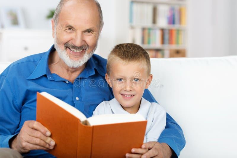 Farfar och sonson som tillsammans tycker om en bok royaltyfria foton