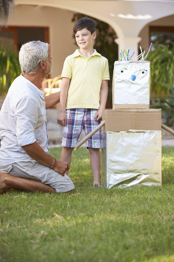 Farfar- och sonsonbyggnadsmodell Robot In Garden arkivbilder