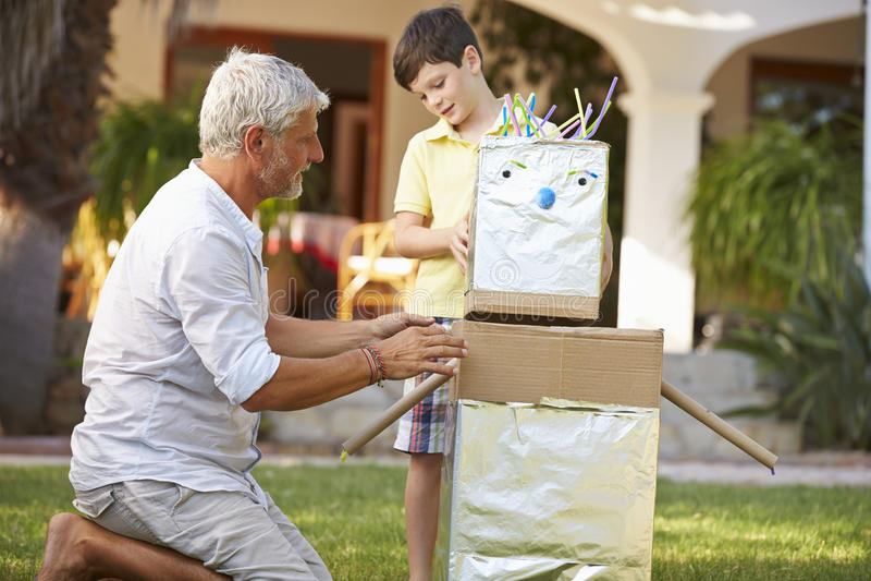 Farfar- och sonsonbyggnadsmodell Robot In Garden fotografering för bildbyråer