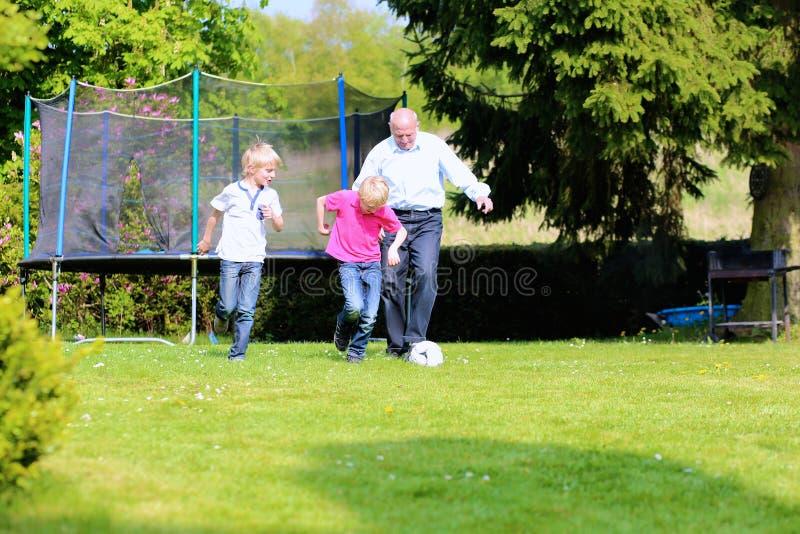 Farfar och sonsoner som spelar fotboll i trädgården royaltyfri fotografi