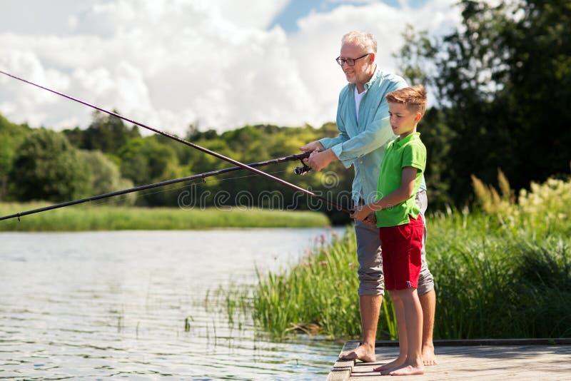 Farfar- och sonsonfiske på flodhytten arkivbild