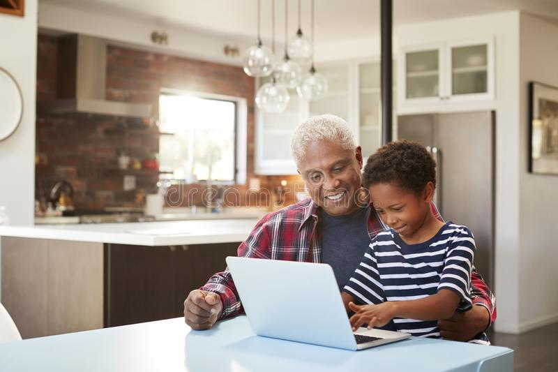 Farfar- och sonsonsammanträde runt om den hemmastadda användande bärbara datorn för tabell tillsammans royaltyfri foto