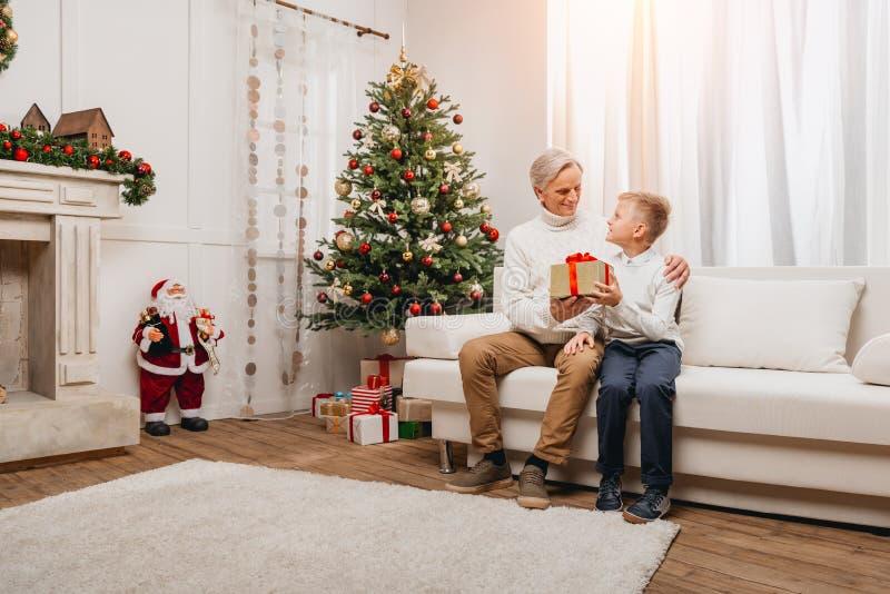 Farfar som framlägger julgåvan till sonsonen royaltyfria foton