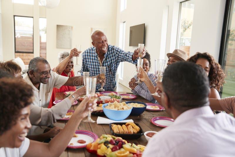 Farfar som gör ett rostat brödanseende på matställetabellen som firar med hans familj, slut upp arkivfoto