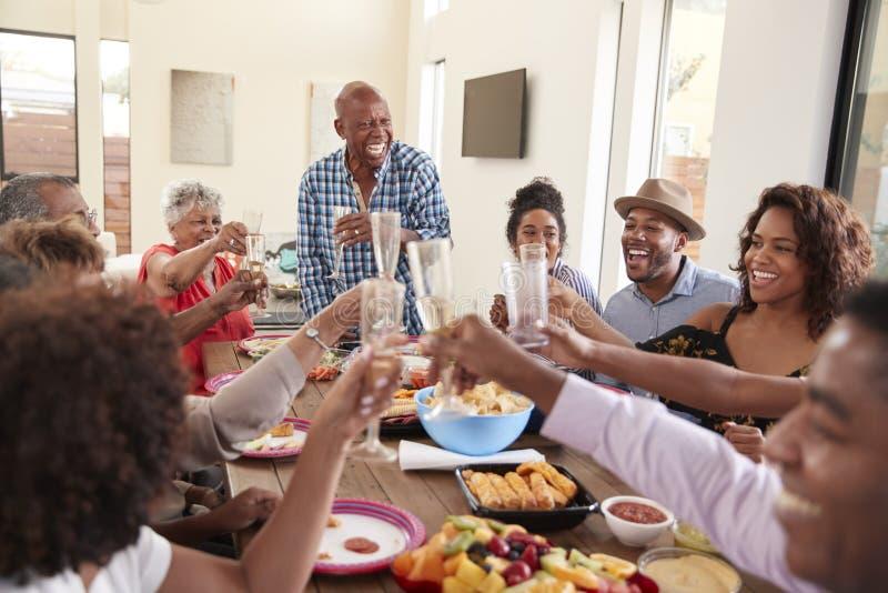 Farfar som gör ett rostat brödanseende på matställetabellen som firar med hans familj, slut upp fotografering för bildbyråer