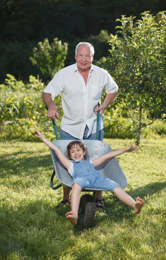 Farfar som ger sondotterritt royaltyfri fotografi