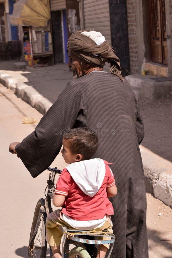 Farfar som kör sonsonen på cykeln arkivbild