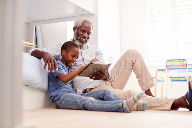 Farfar som sitter med sonsonen i det Childs sovrummet genom att använda den Digital minnestavlan tillsammans arkivbild