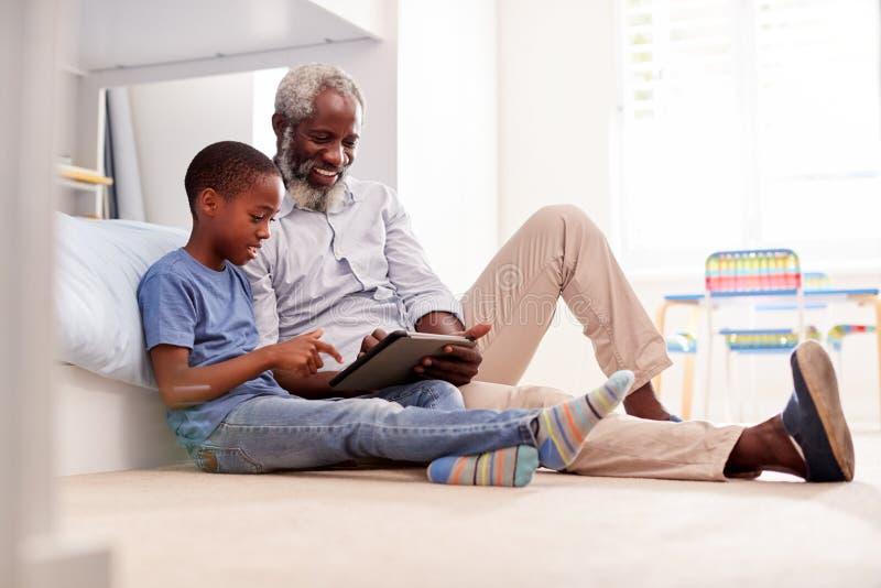 Farfar som sitter med sonsonen i det Childs sovrummet genom att använda den Digital minnestavlan tillsammans royaltyfri bild