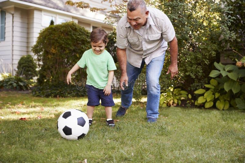 Farfar som spelar fotboll i trädgård med sonsonen royaltyfri bild