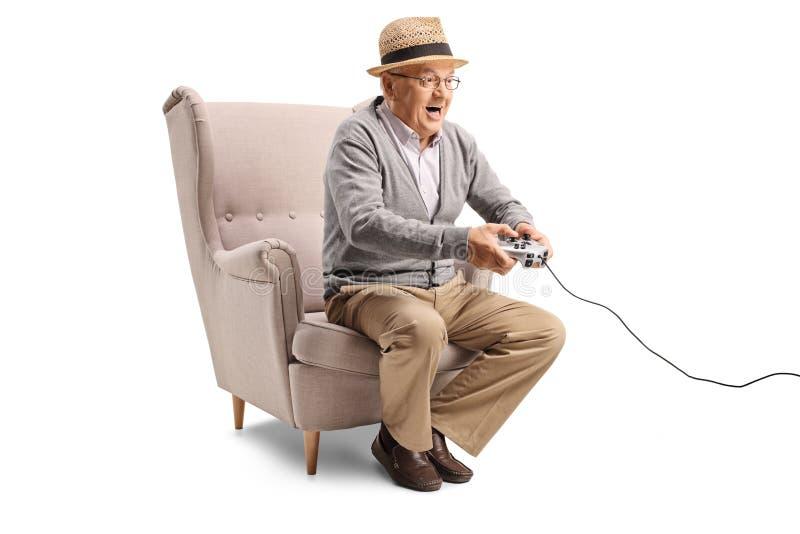 Farfar som spelar videospel arkivfoto