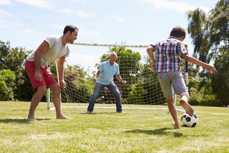 Farfar-, sonson- och faderPlaying Football In trädgård royaltyfri foto