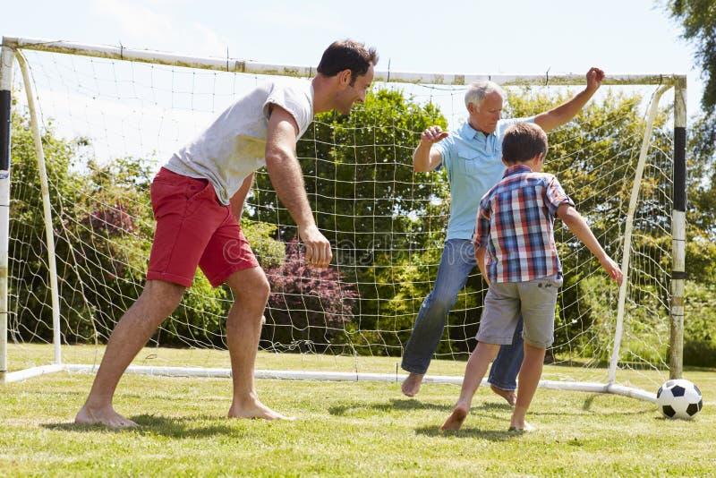 Farfar-, sonson- och faderPlaying Football In trädgård arkivbilder