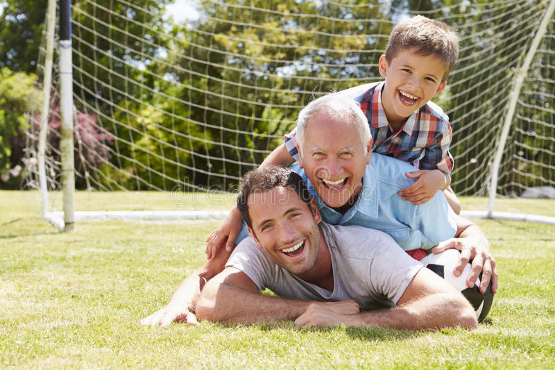 Farfar-, sonson- och faderWith Football In trädgård royaltyfria bilder