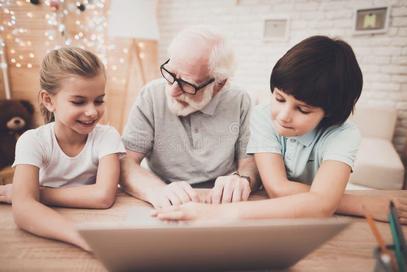 Farfar, sonson och sondotter hemma Morfadern och barn använder bärbara datorn royaltyfri fotografi