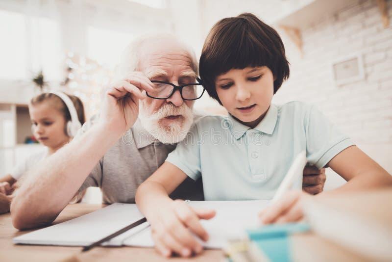 Farfar, sonson och sondotter hemma Morfadern hjälper pojken med läxa arkivfoton
