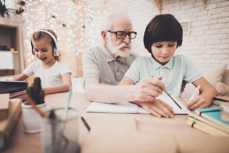Farfar, sonson och sondotter hemma Morfadern hjälper pojken med läxa royaltyfria foton