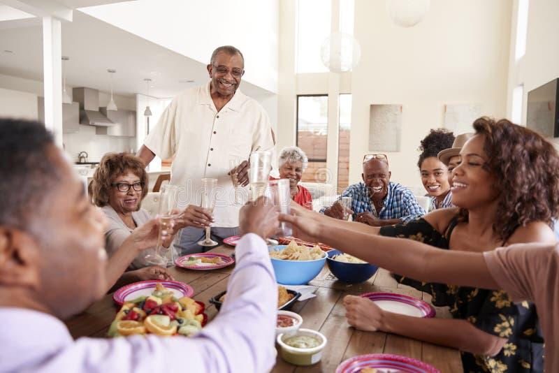 Farfaranseende som gör ett anförande på tabellen med hans familj, slut upp royaltyfria foton