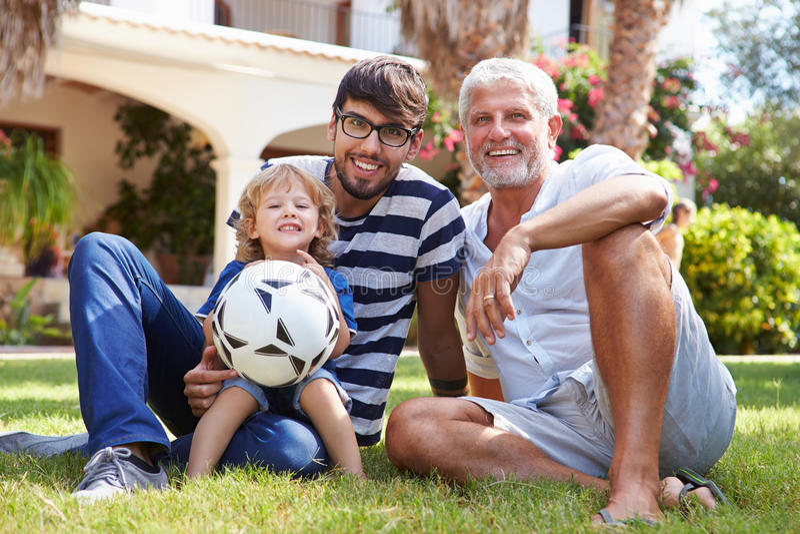 Farfarsammanträde i trädgård med sonen och sonsonen fotografering för bildbyråer
