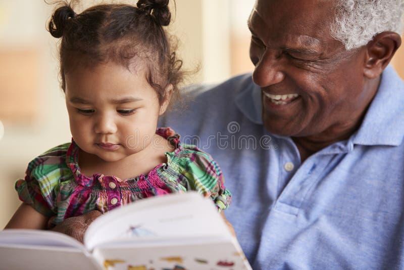 Farfarsammanträde på den Sofa At Home With Baby sondotterläseboken tillsammans royaltyfria bilder