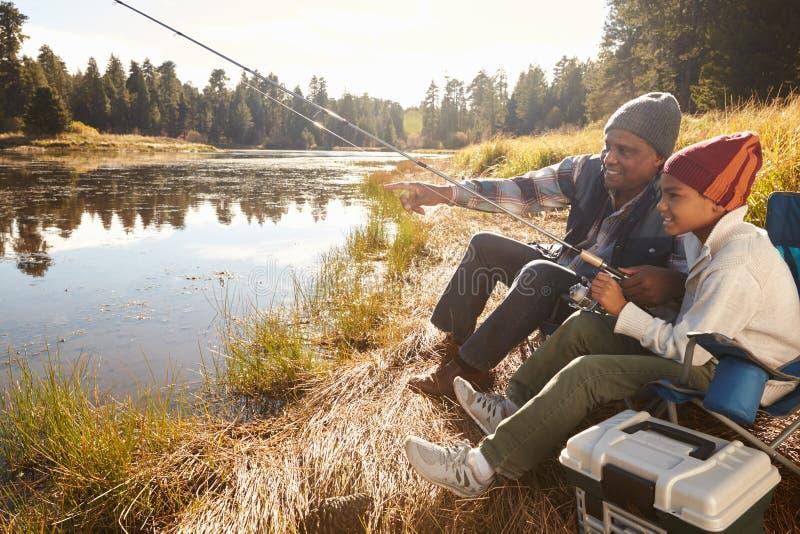 Farfarundervisningsonson som fiskar vid sjön royaltyfria bilder