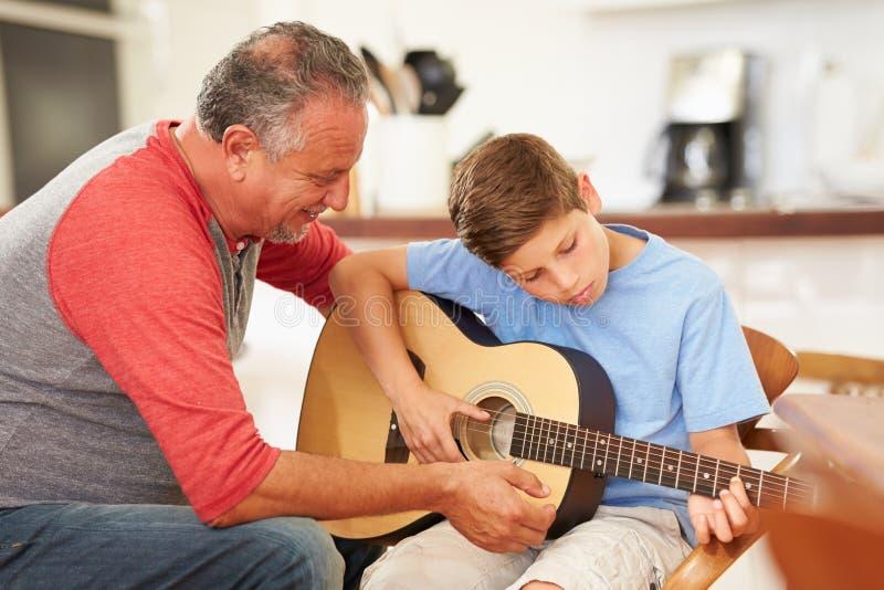 Farfarundervisningsonson som spelar gitarren royaltyfri fotografi