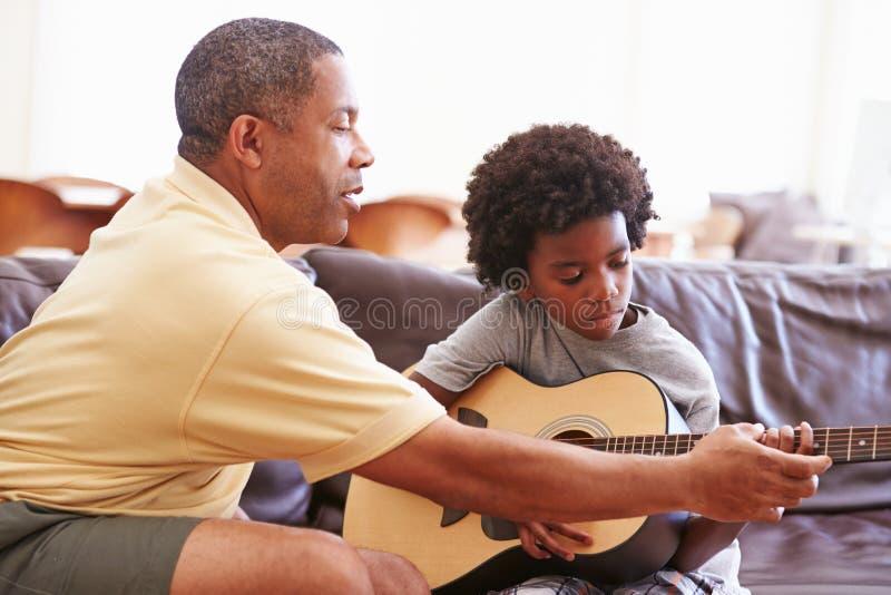 Farfarundervisningsonson som spelar gitarren royaltyfri foto