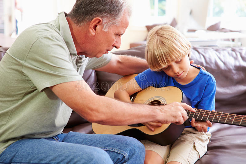 Farfarundervisningsonson som spelar gitarren royaltyfria bilder