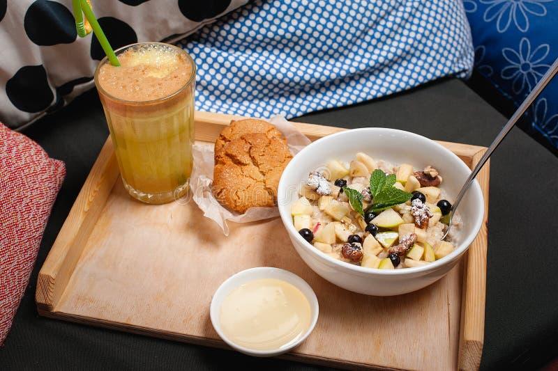 Farina d'avena della prima colazione con frutta, i biscotti ed il succo fresco immagine stock