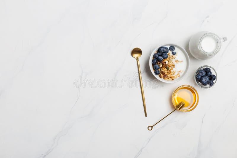 Farina d'avena dello spazio libero con latte, i mirtilli ed il miele fotografie stock