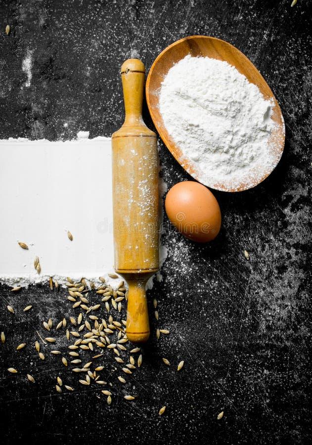Farina di frumento con l'uovo, il matterello ed il grano fotografia stock libera da diritti