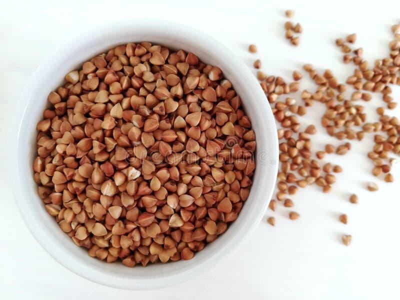 Farina di grano saraceno organica in una ciotola ceramica bianca Ingrediente per la prima colazione sana fotografie stock libere da diritti