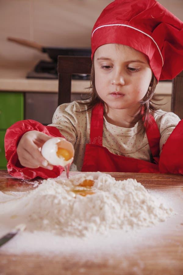 Farina ed uova Il piccolo panettiere sveglio della ragazza del bambino ha preparato la farina per cuocere immagini stock