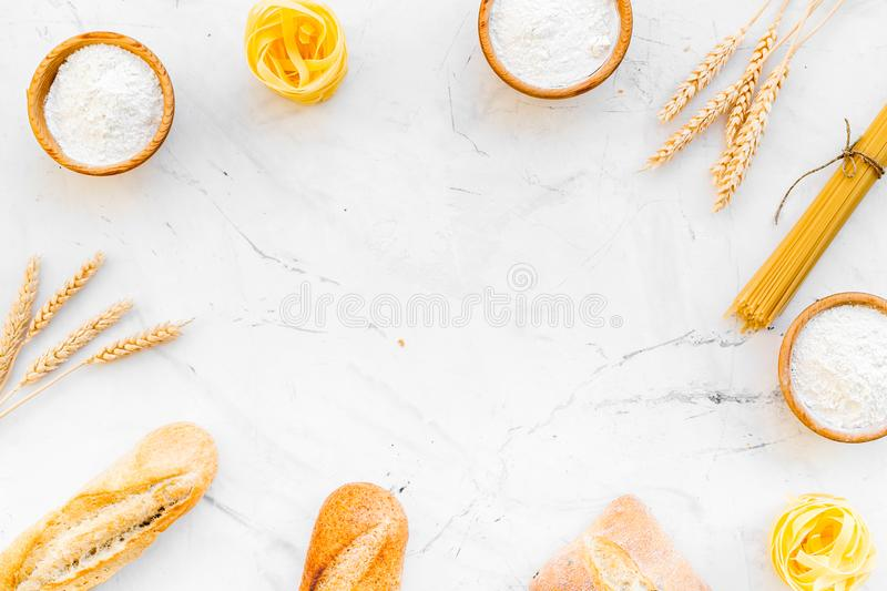 Farinaceous food. Fresh bread and raw pasta near flour in bowl and wheat ears on white stone background top view copy stock photos