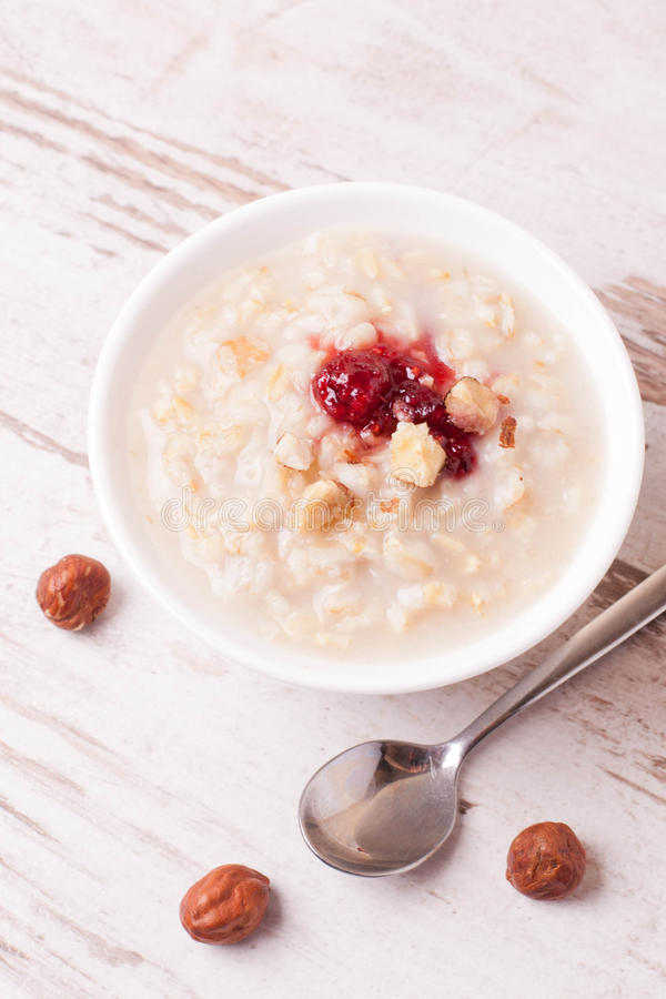 Farine d'avoine avec du lait, écrous et confiture de fraise et cruche de lait images stock