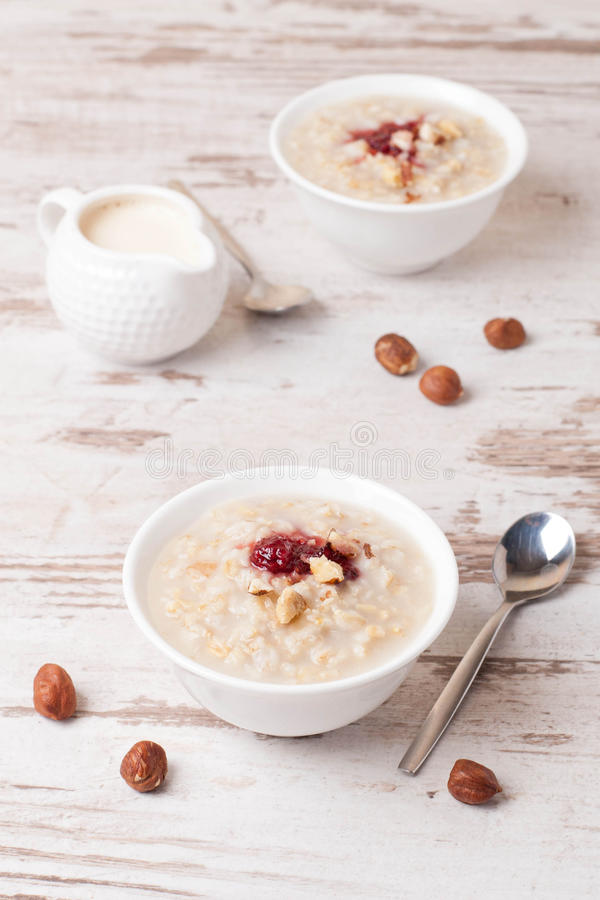 Farine d'avoine avec du lait, écrous et confiture de fraise et cruche de lait sur le t images libres de droits