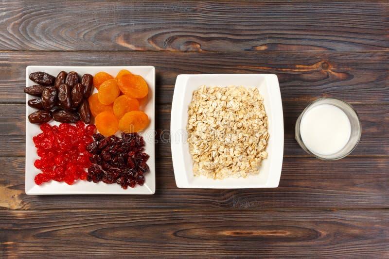 Farine d'avoine avec du lait et des fruits secs Fond en bois foncé de petit déjeuner utile et sain, vue supérieure photographie stock libre de droits