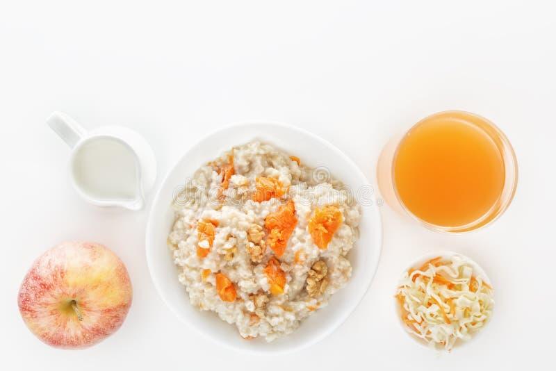 Farine d'avoine avec le potiron et les écrous, la salade, un verre de jus frais, une pomme et une cruche de lait sur un fond blan photo libre de droits