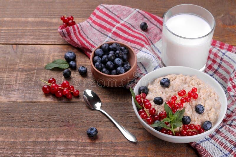 Farine d'avoine avec les baies et le lait sur une table en bois brune Nourriture saine de petit déjeuner photos libres de droits